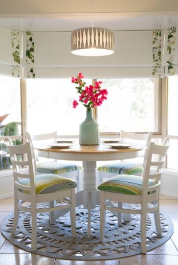The beautiful circular wooden dining table and its white wooden chairs are illuminated by the surrounding bright glass windows with shades in this bright and cozy Cottage-style dining room.