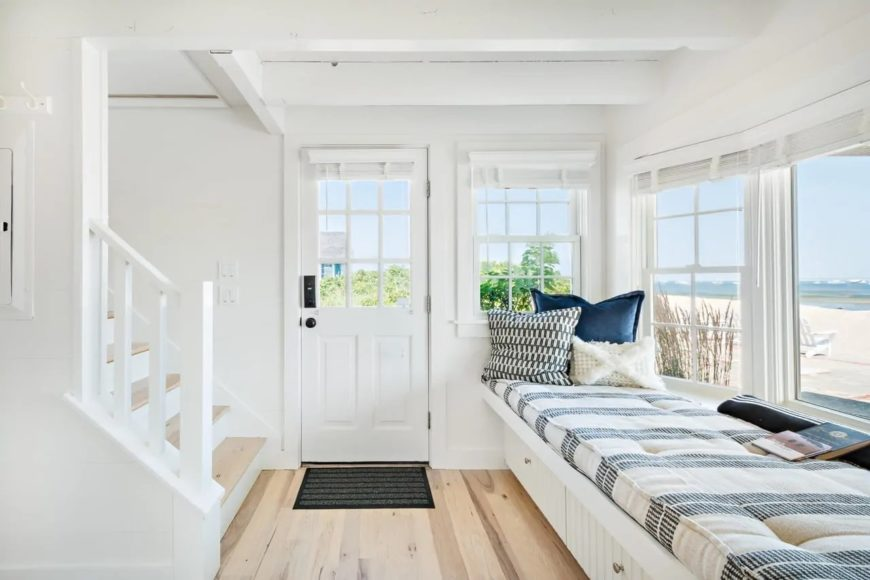 The bright natural lights give this Cottage-style foyer a sunny demeanor to welcome the guests. There is also a comfortable cushioned sitting area on the side with a built-in bench below the window that could also serve as a reading nook.