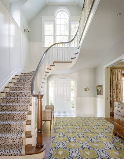 This is a bright and welcoming Cottage-style foyer with a white main door flanked with glass side lights bringing in natural lighting that brightens up the white wainscoting. This is then complemented by light gray upper walls and a patterned carpeting.