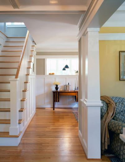 The hardwood flooring of this Cottage-style foyer matches well with the wooden steps of the staircase and the wooden console table that stands out against the white wainscoting and white walls. This pairs well with the white ceiling.