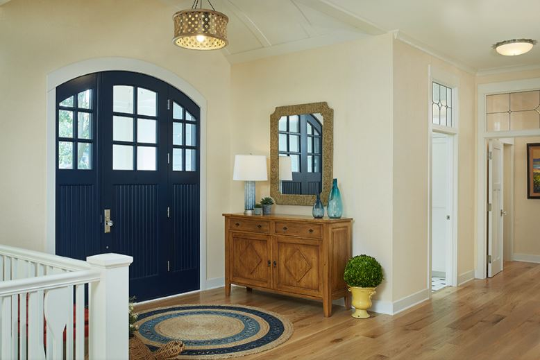 This Cottage-style foyer has a dark blue arched main door with matching side-lights. This set stands out against the light beige walls, light hardwood flooring and the white cove ceiling. This ceiling hangs a circular golden pendant light over the circular area rug.