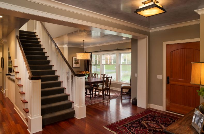 This elegant Cottage-style foyer has a wooden main door matching the dark hardwood flooring that is complemented by the deep red patterned area rug. The light gray walls match well with the gray carpeting of the wooden staircase leading to the next level of the house.