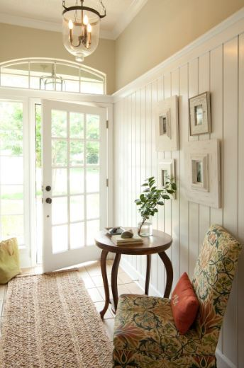 The main door of this Cottage style foyer is dominated by small glass panels that match with its side-lights and arched transom window. These bring in natural lights that brighten the white wooden walls and tiled flooring topped with a brown area rug.