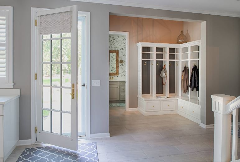 The light gray walls of this Cottage-style foyer are complemented by the white details of the molding and the white wooden L-shaped mudroom with drawers shelves and a place to hang coats separately in each cubicle.