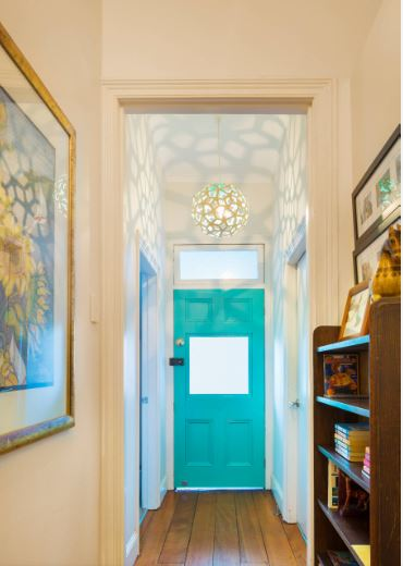 The brilliant pastel blue wooden main door of this Cottage-style foyer goes quite well with the beige walls and dark hardwood flooring. These are complemented by the shadows and warm lights made by the decorative spherical pendant light.