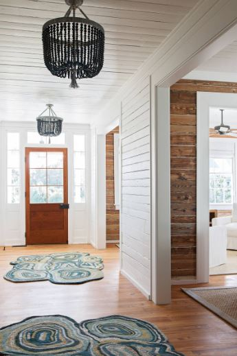 The white shiplap wooden ceiling of this hallway-like Cottage-style foyer is a good match for the white walls. These are balanced by the hardwood flooring with patterned area rugs and the wooden door surrounded by bright glass windows.