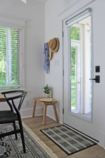 This is a rather small but charming Cottage-style foyer with a door dominated by the large glass panel in the middle that brings in natural lights for the white walls and light hardwood flooring. Beside the door is a small wooden bench topped with built-in hooks for the hats and coats.
