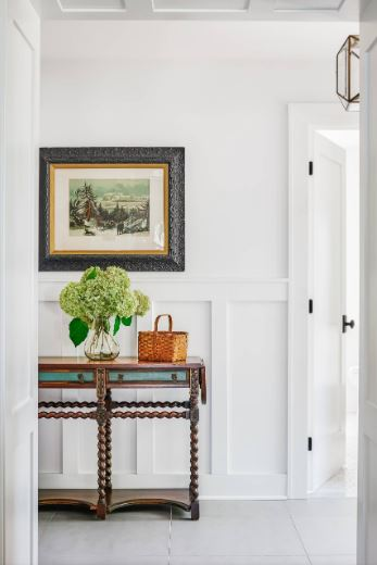 The bright white walls, white wainscoting and white ceiling make up for the small floor space of this Cottage-style foyer. This is then balanced by the dark wooden console table and the small colorful painting mounted on the wall above it.