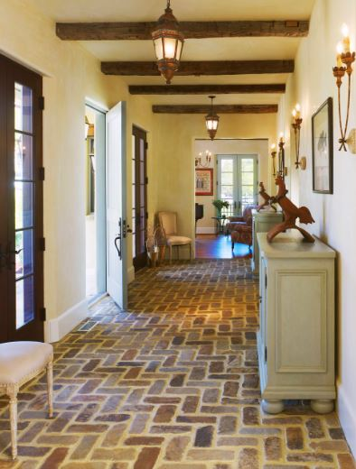 The beige ceiling has exposed dark wooden beams that go quite well with the mosaic brick flooring of this Cottage-style foyer. These are complemented by the charming pendant lantern lights and the various decors mounted on the beige wall.