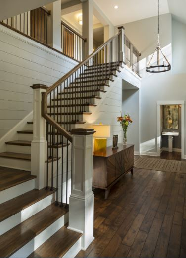 The round wooden chandelier that hangs from the high ceiling is a perfect match for the dark hardwood flooring of this Cottage-style foyer. It also blends with the dark wooden low cabinet and the steps of the wooden L-shaped stairs leading to the next level.