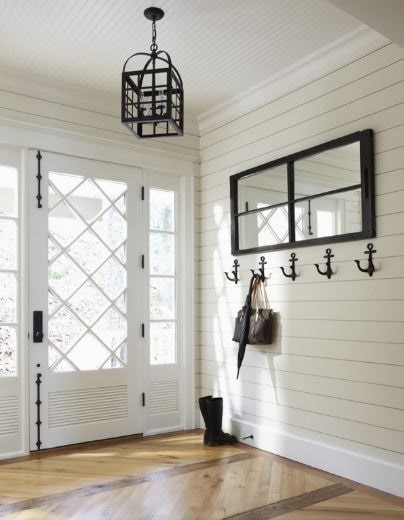 This is a simple Cottage-style foyer with wrought iron hooks that look like anchors mounted on the beige shiplap wall by the main door. These matches well with the dark frames of the mirror and the wrought iron lantern pendant light that dominates the white ceiling.