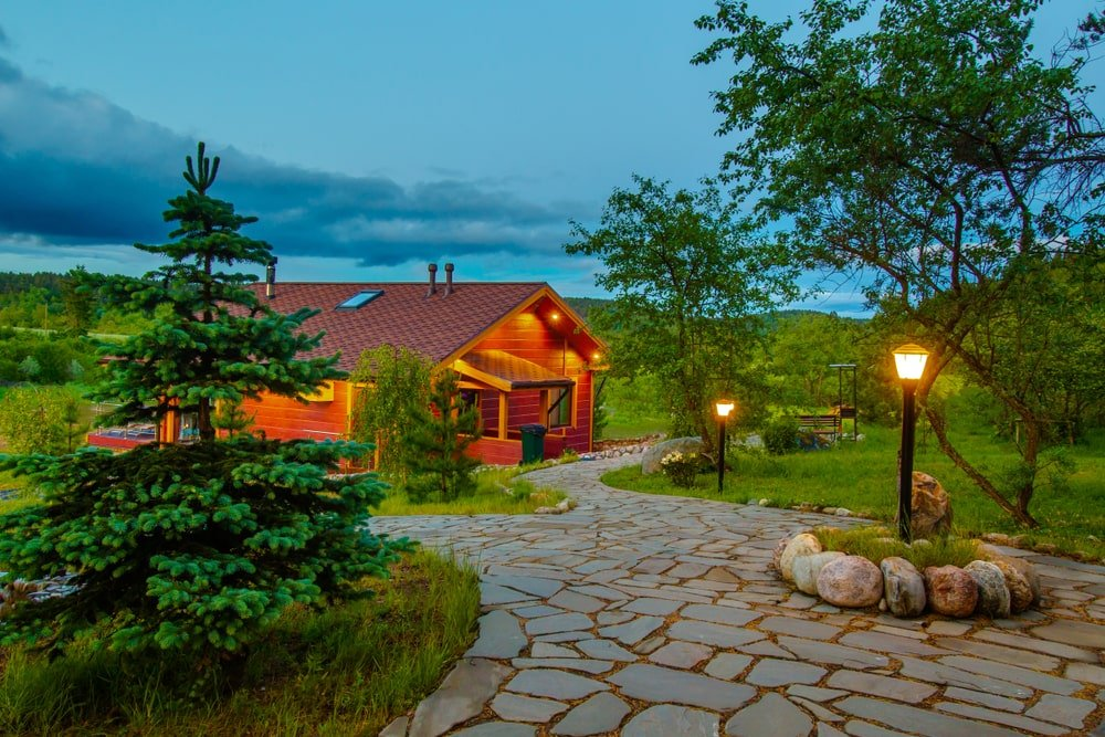 The inclined walkway leading to the home is made of mosaic gray stone slabs decorated with a number of small lamp posts, medium-sized trees, pines and decorative rocks that seem to enhance the natural landscape that surrounds the brilliant red home.