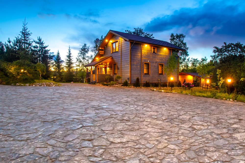 The walkway and driveway leading to the house is made of textured mosaic gray stones perfectly matching with the gray exterior walls of the home that is lit with a warm glow from the yellow lights. There are also similar lights from small lamp posts lining the lawns of grass and shrubs.
