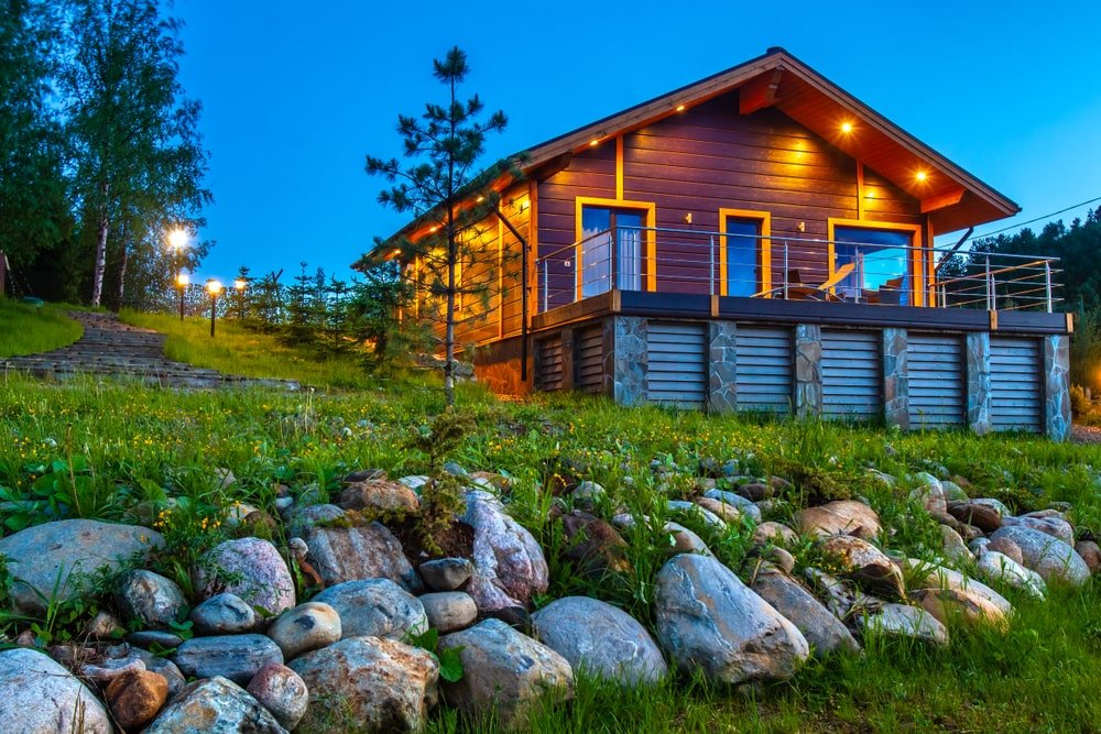 The dark brown wooden exterior walls of the home is complemented by the warm yellow lights giving it an ethereal glow that cascades down onto the surrounding landscape filled with tiny yellow flowers, grass, shrubs and tall pine.