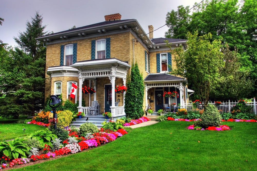 This Cottage-style landscaping is filled with colorful flowers and shrubs giving it a vibrancy that goes well with the deep green carpet of grass, tall trees and creeping plants that provide a lively aura to the brown bricks of the home exterior.