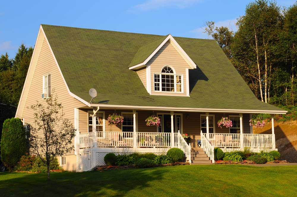 This gorgeous home has a moss green tone to its roof that pairs quite well with the carpet of well-manicured grass of the front lawn. This has various shrubberies that line the side of the home flanking the small stairs to the front porch decorated with hanging flower pots.