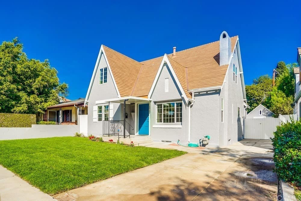 This is simple Cottage-style landscaping with a small plot of land planted with a vibrant green carpet of grass with a few small flowering plants peppered at the edge near the entryway of the home that has a bright blue wooden main door.