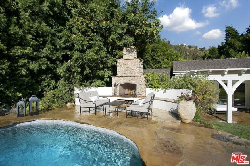 There is an outdoor fireplace near the edge of the pool where people can warm themselves as they seat on the outdoor sofas. This area is decorated by various shrubs, tall trees and a potted plant.