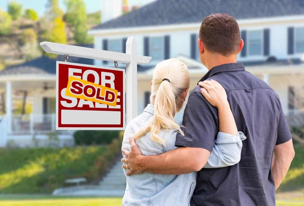 A couple links arm while facing a beautiful home with a signage that says it's already sold.