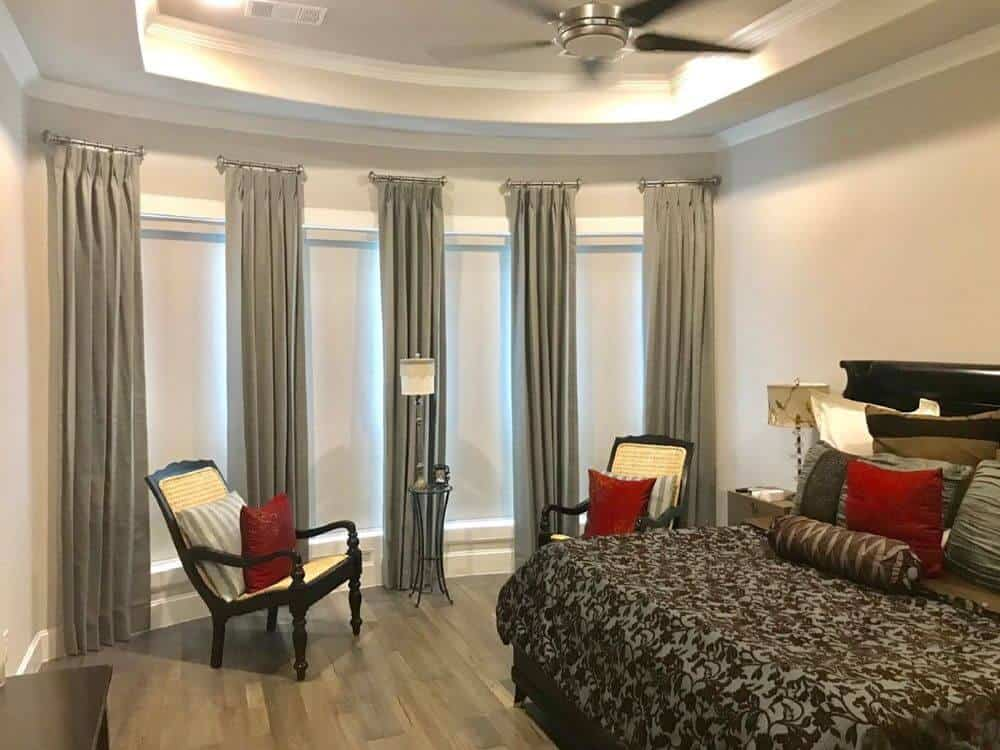 This primary bedroom offers a gorgeous bed setup along with a tray ceiling and hardwood flooring. The windows also offer drapery.