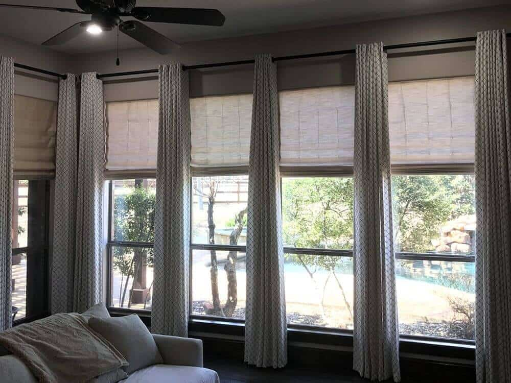 A focused look at this living space's panel windows drapery. The area has gray walls and hardwood floors.