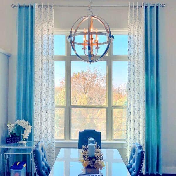 This dining room offers a beautiful dining table and chairs set lighted by a charming ceiling light. The window features lovely blue and white drapery.