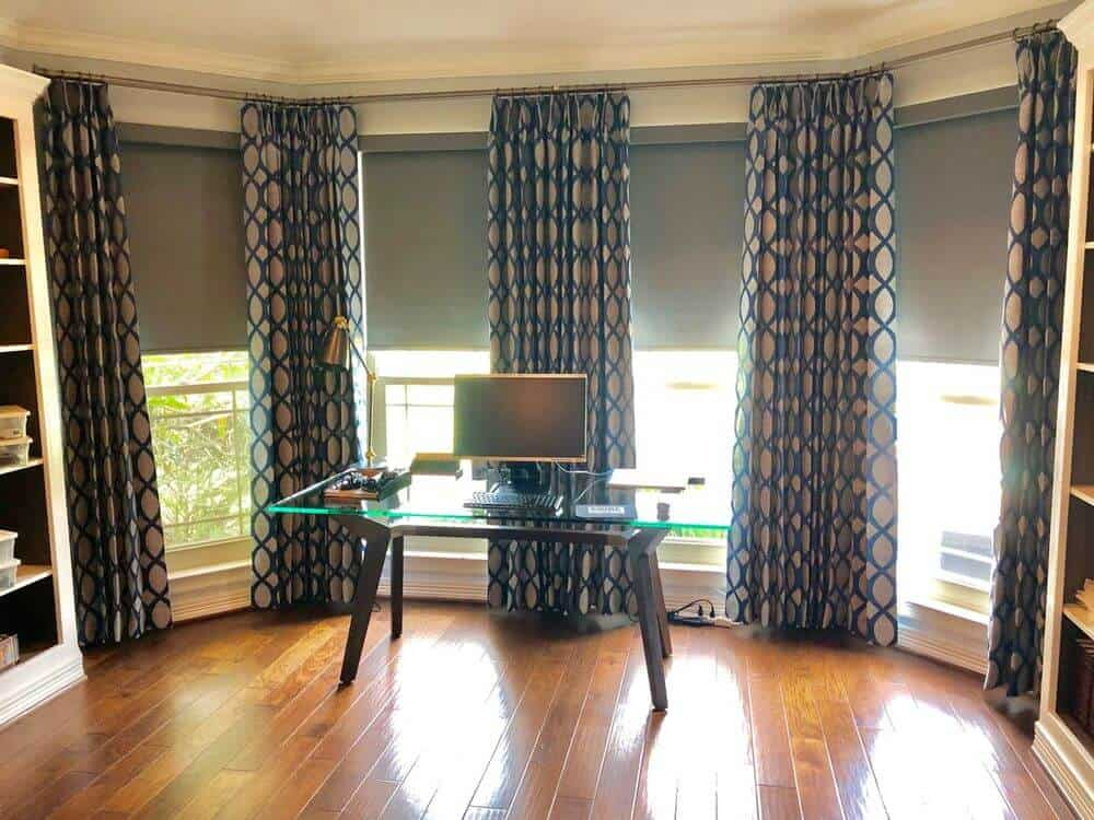 A spacious home office featuring hardwood floors and windows with custom drapery that look stylish. There are shelving on both sides and a glass top office desk in between.