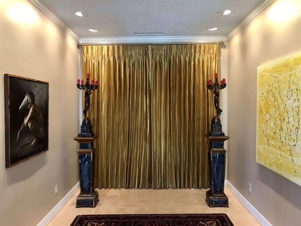 This elegant hallway features artistic wall decors and gorgeous lighting, along with a stunning drapery. The area also features beige tiles flooring.