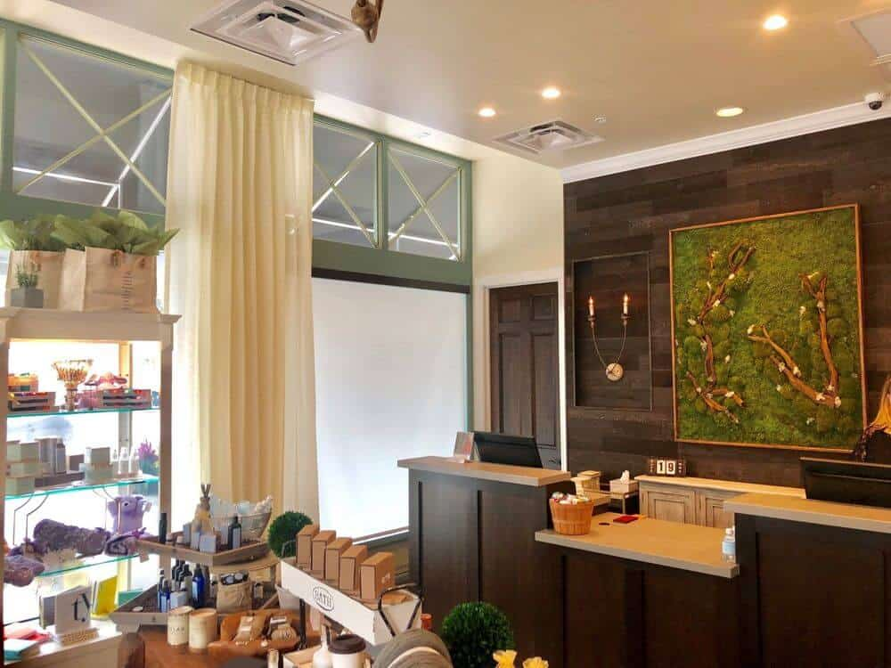 This store features custom drapery, a tall ceiling with recessed lights and beige walls.