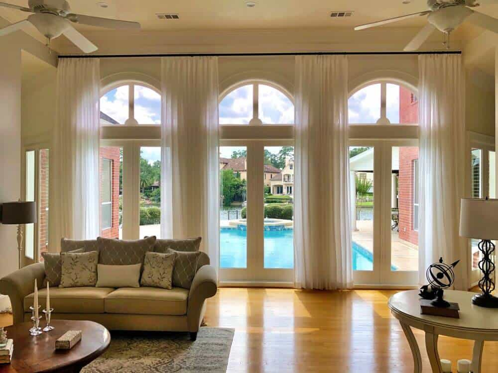 A formal living room with classy seats and other furniture sets, along with a tall ceiling and large windows featuring custom drapery.
