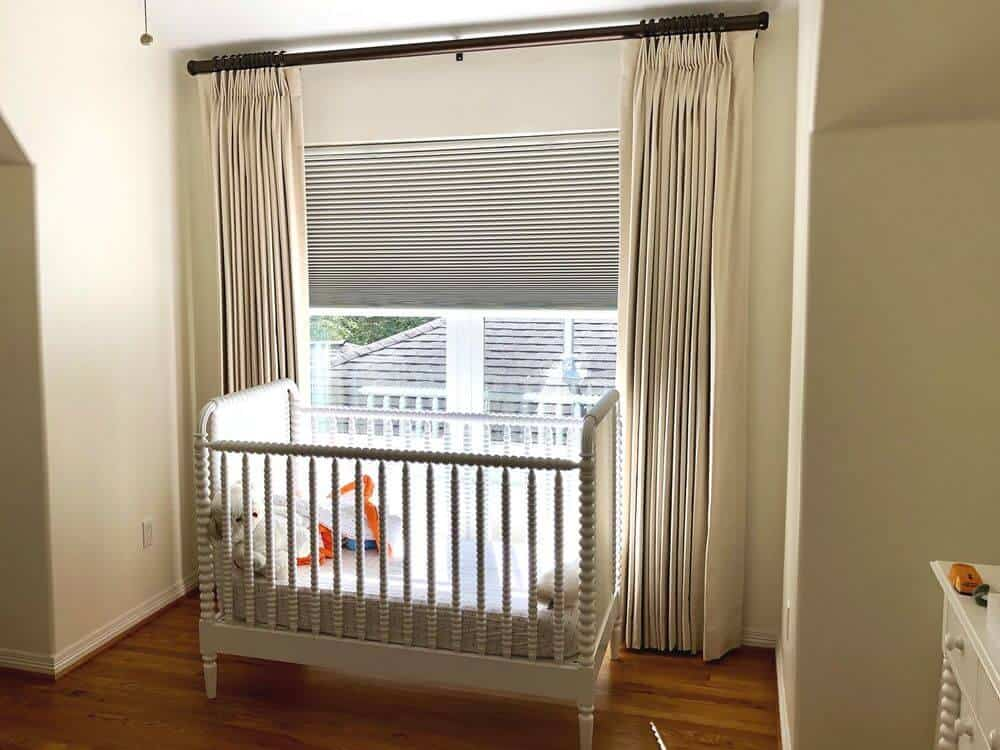 A nursery room offering a nursery bed set near the window, which features a custom drapery.
