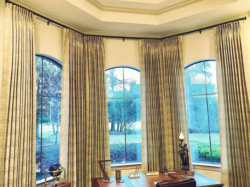 A focused look at the beautiful drapery of this elegant home office. The gorgeous windows, beige walls and tray ceiling can also be seen in this view.