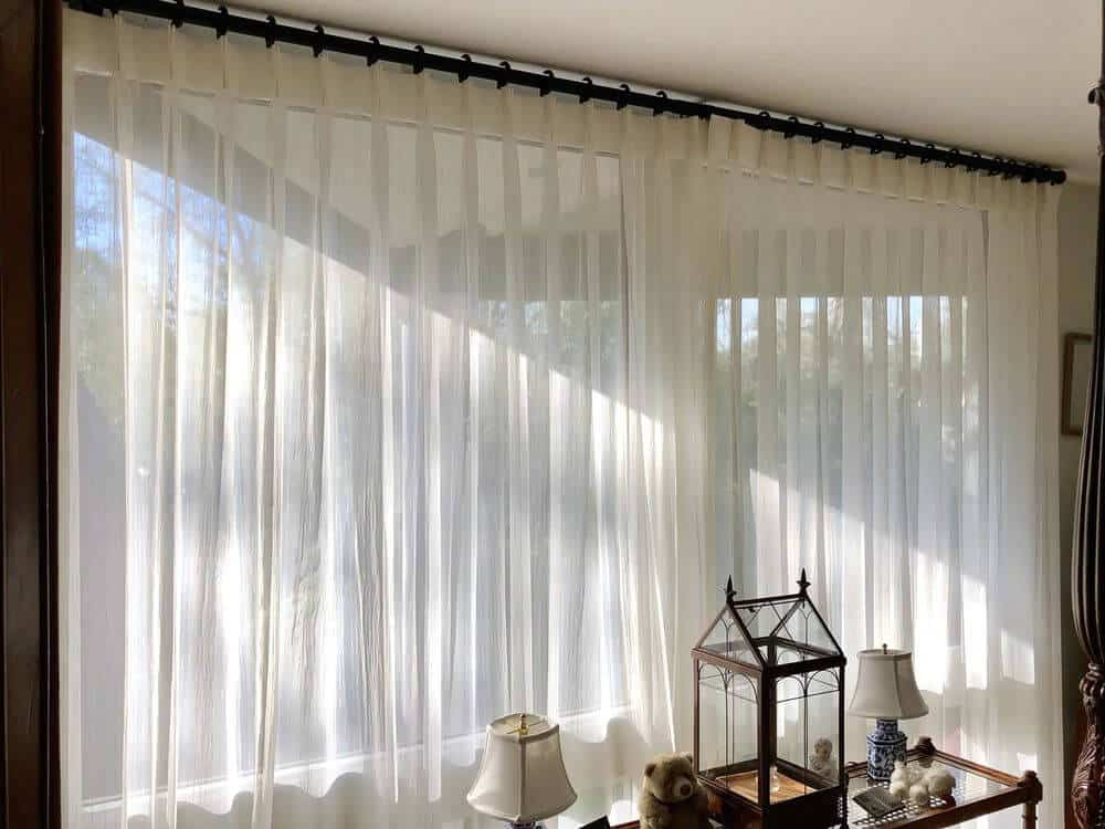 A closer look at an example of a wide width sheer drapery installed in a wide glass window.