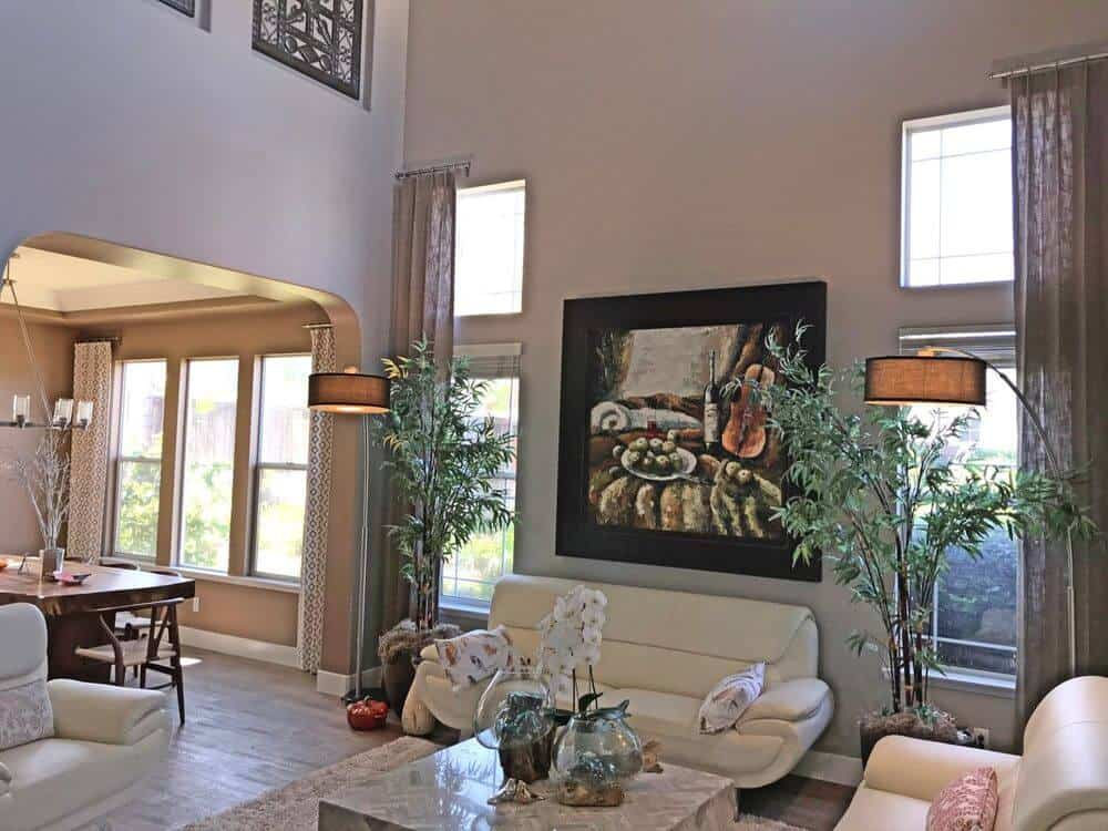 A formal living space set under the home's high ceiling. The area has hardwood floors and gray walls, along with comfy seats and a stunning center table on top of an area rug.