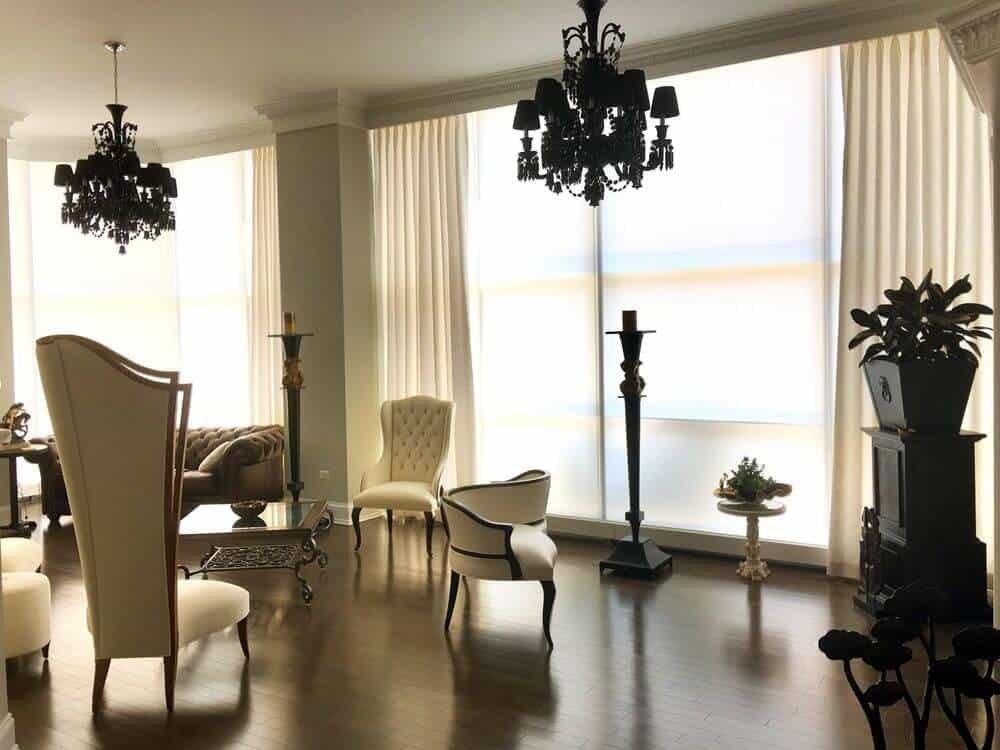 A formal living space boasting a set of elegant furniture and chandelier lighting. The area also features large windows with custom drapery.