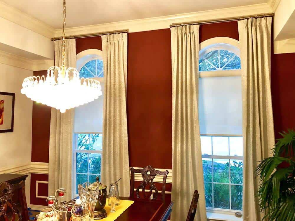 Dining room boasting an elegant dining table and chairs set surrounded by classy walls and lighted by a luxurious chandelier. The windows also feature gorgeous drapery.