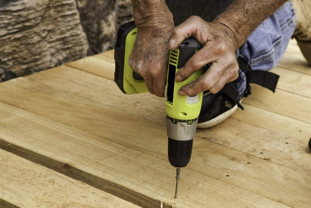 A carpenter driving a long screw into a wooden deck with a drill.