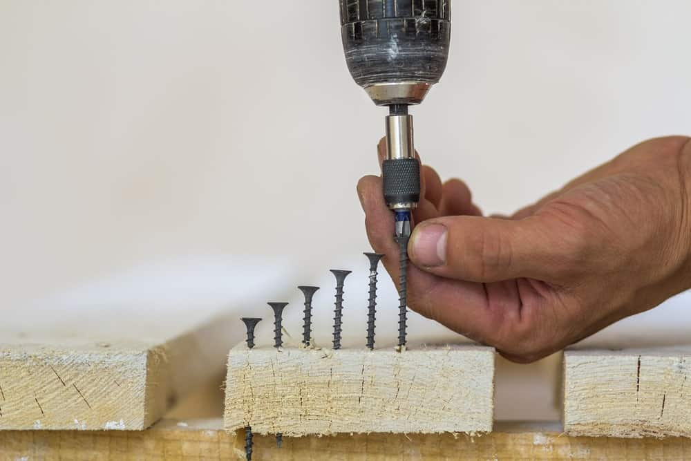 A carpenter driving a row of wood screws into a piece of wood. with varying heights.