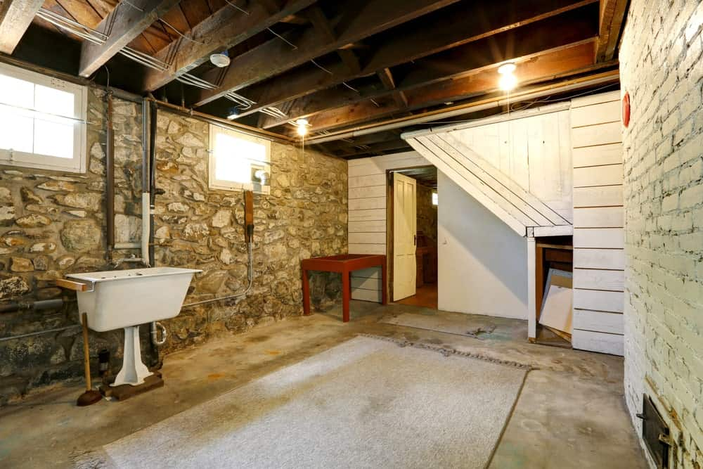 An empty basement featuring stone and brick walls along with a rustic ceiling with several exposed wooden beams.