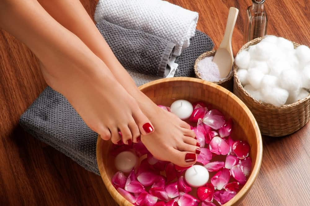 Pedicured feet on a bowl filled with water and flower petals for the foot spa.