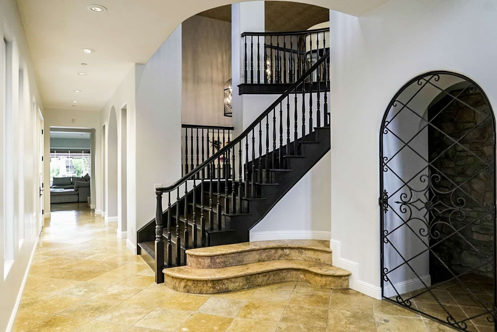 An entry featuring beige tiles flooring. It showcases a staircase on the side leading to the basement, and another staircase leading to the second floor. Images courtesy of Toptenrealestatedeals.com.
