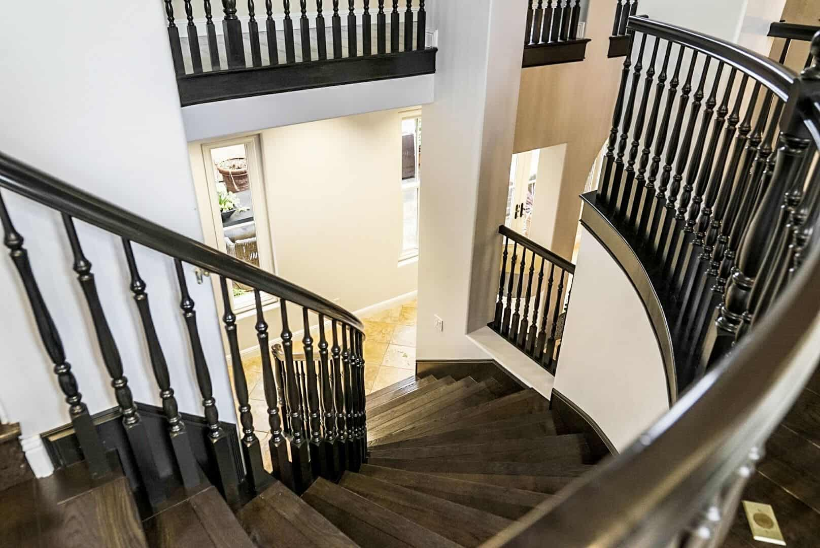 A focused look at the home's curved wooden staircase set near the entry, featuring classy railings. Images courtesy of Toptenrealestatedeals.com.