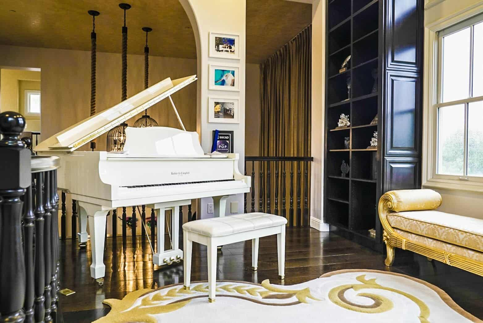 On the second floor, there's a small living space featuring a classy seat on the side along with a white grand piano. The hardwood flooring is topped by an elegantly-designed area rug. Images courtesy of Toptenrealestatedeals.com.