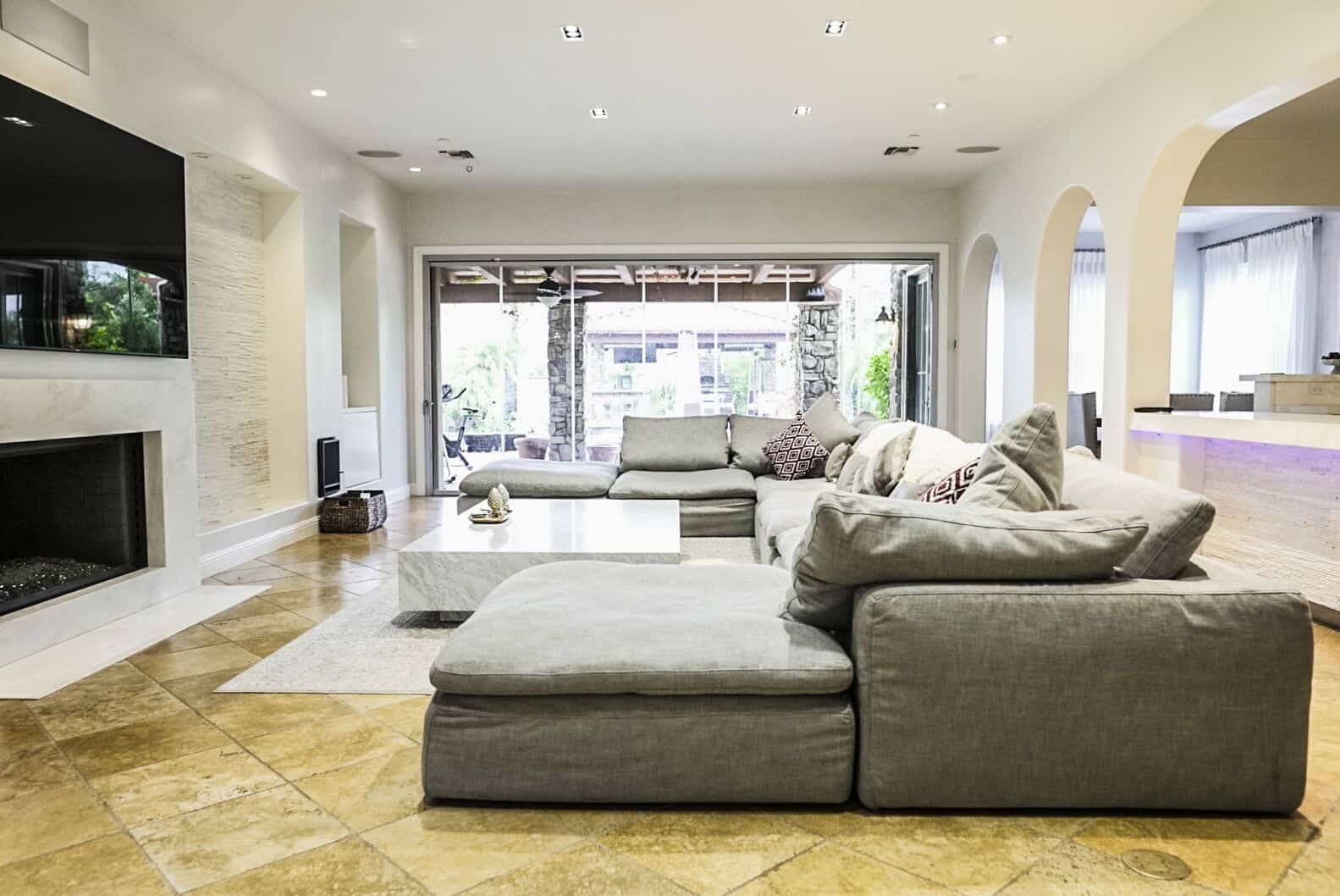 The house's family living space offers a large comfy sofa set and a large marble center table set on top of an area rug covering the beige tiles flooring. There's a fireplace and a large flat-screen TV as well. Images courtesy of Toptenrealestatedeals.com.