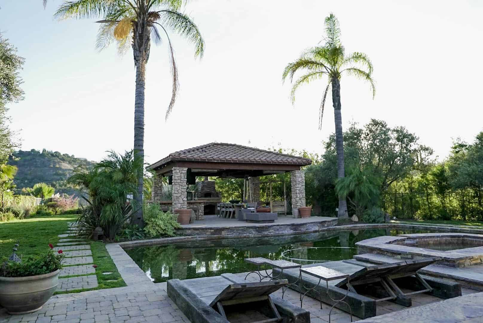Here's the view of the swimming pool with a modern cabana on the side featuring an outdoor dining and kitchen. Images courtesy of Toptenrealestatedeals.com.