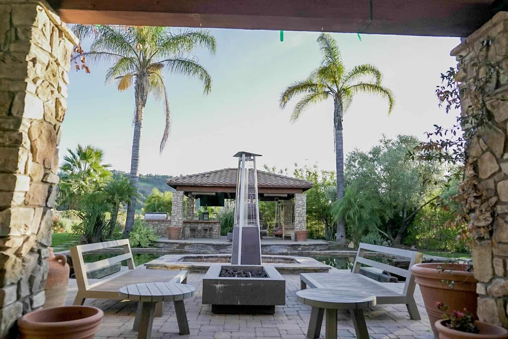 This patio in the backyard boasts a pair of large seats with a fire pit in the middle. It is also set near the swimming pool. Images courtesy of Toptenrealestatedeals.com.