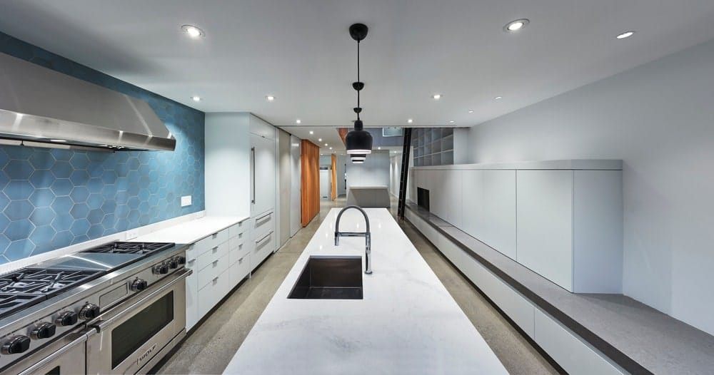 A large and stunning contemporary galley-style kitchen boasting blue tiles backsplash and has a long white center island lighted by stylish pendant lights.