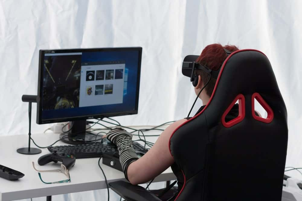 Back view of a person playing VR on a gaming chair.