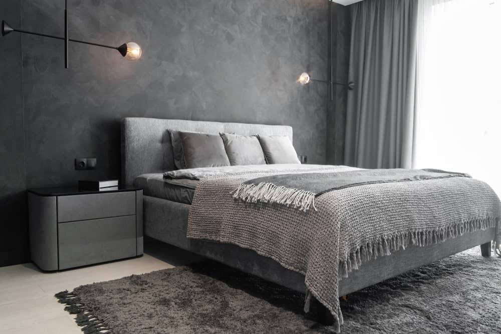 Gray primary bedroom with modern design featuring concrete walls, wide plank flooring, contemporary furniture, industrial lamps, tasseled rugs and throws.