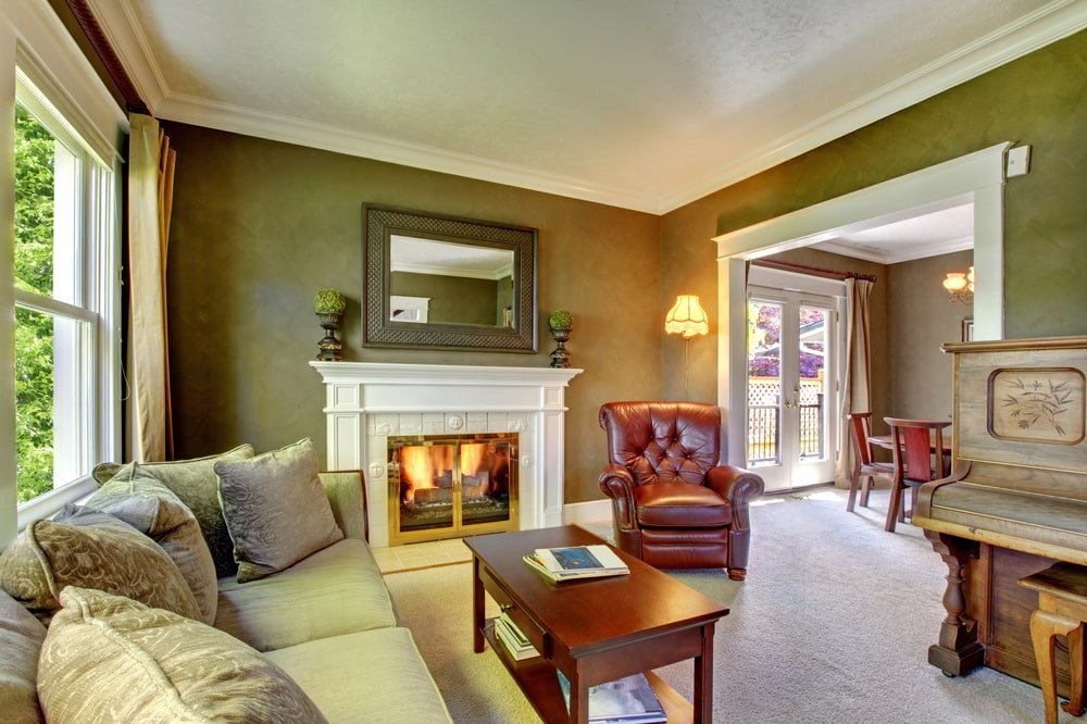 Green living room with a vintage piano, traditional fireplace and carpet flooring.